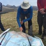 Gids Colin buigt over de kaart om ons aan te wijzen welke eilanden we zien liggen in de verte